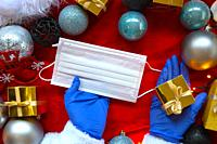 Christmas decoration with medical blue gloves and protective face mask for COVID-19, hand holding mask and golden present, coronavirus and Christmas c...