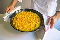 Chef holding a paella with Arroz del Señorito. Valencia, Spain.