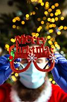 Man holding glasses with Merry Christmas and wearing protective safety mask and gloves for Coronavirus, Covid-19 and Holiday concept background.