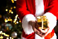 Man in Santa Claus costume near Christmas tree holding a golden gift box, Christmas present background with bokeh lights beauty.
