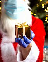 Santa Claus is holding a golden gift box wearing protective gloves and a Safety mask for Coronavirus, Covid-19 and Christmas concept present.
