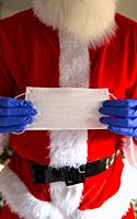 Man wearing santa claus costume holding safety mask and wearing protective gloves for Coronavirus, Covid-19 and Christmas concept close up.