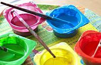 Washable Tempera and rounded paint brushes. Yogurt cups reused as paint containers.