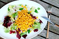 Salad with lettuce and corn on wooden table