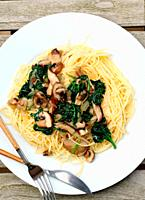 Plate of spaghetti with spinach and mushrooms