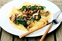 Plate of spaghetti with spinach and mushrooms on wooden table