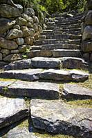 Ancient stone staircase formed by large steps of irregular shape.
