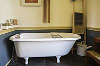 White claw foot bathtub in main bathroom with black ceramic tile floor inside an old 1841 cottage style fieldstone house, Quebec, Canada. This image i...
