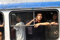 Pyongyang, North Korea, Asia - Commuters look out of an open window of a fuly occupied tram in the centre of the North Korean capital city.