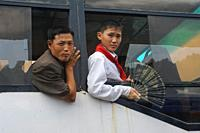 Pyongyang, North Korea, Asia - A man and a boy who is wearing the uniform of the Young Pioneers and holding a hand fan look out the open window of a b...