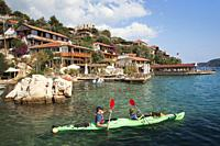 Father and son on Kayak in front of the traditional houses of the ancient Simena todays Kalekoy, Ucagiz Town, Antalya Region, Lycian Coast, Turkish Ri...