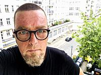 Berlin, Germany. Self Porttrait (selfie) of a beglassed man with very short hairdue standing on a third floor balcony with view to a Karl Marx Allee a...