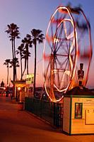 A fast spinning Ferris wheel is illuminated along the amusement area of Balboa Island in Newport Beach, California.
