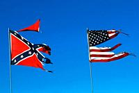 Tattered and torn American flag flies along side a southern confederate flag.