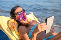 Woman wearing mask and reading tablet on the beach in covid times.