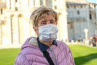 elderly woman wearing face mask visiting famous landmark.