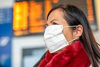 Woman with face mask at the airport in front of departure board.