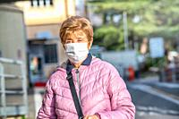 elderly woman wearing face mask visiting city hospital.