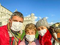 Family of three people wearing face mask visiting famous landmark.