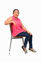portrait of a woman sitting on a chair with the body in profile and looking at the camera on white background,.