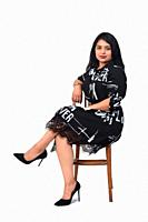 latin woman with dress and high heels sitting on chair on white background, legs crossed.