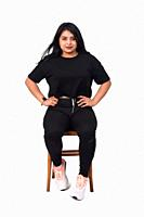 front view of a latin woman sitting on a chair white background, hands on hip.