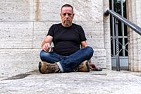 Berlin, Germany, Portrait of a mature adult, caucasian male sitting against a grey wall.