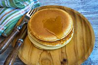 Homemade pancakes on a wooden plate.