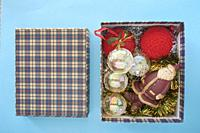 Christmas Decoration In A Box some different christmas ornaments in a box, on a blue background.