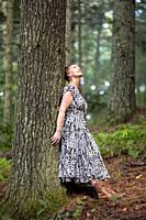 Joyful woman leaning against tree in the forest looking up in wonder - Brevard, North Carolina, USA.