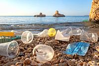 RED SEA, SHARM EL SHEIKH, EGYPT - OCTOBER 18-26, 2020: Plastic debris and face masks on the beach in surf zone. Coronavirus COVID-19 is contributing t...