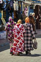 three women walking in the medina, Essaouira, Morocco.
