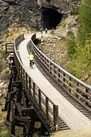 A bicyclist near a tunnel in the Myra Canyon, on the Kettle Valley Rail Trail, Okanagan, British Columbia, Canada.