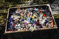 West Cornwall, Ct. USA A dumpster filled with discarded books at an old bookstore going out of business.