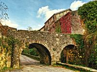 stone bridge over Rue de la Cale, Puy-lEveque, Lot Department, Occitanie Region, France.