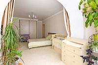 View from the glazed loggia to the interior of a spacious bedroom with furniture for a newborn baby.