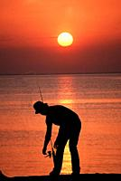 Silhouette of Fisherman at sunset Venice Florida.