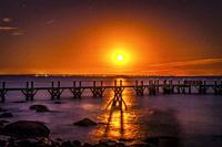 Orange Moon Blue Water Night Stars Beach Pier Buzzards Bay Ocean Padanaram Dartmouth Massachusetts New Bedford Lights in distance.