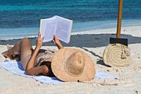 Portrait of a young woman relaxing on the beach, reading a book.