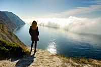 A girl stands on a hill and observes an unusual phenomenon of nature over the sea.