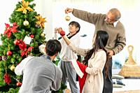 Multigenerational asian Family decorating a Christmas tree. Mom Dad daughter girl and grandfather decorate the Christmas tree prepare for season greet...