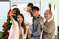 Multigenerational asian Family ,Mom Dad daughter girl and grandfather ,selfie with a Christmas tree after decorate the Christmas ornament prepare seas...