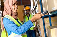 Asian Islam Muslim female warehouse worker do inventory with barcode scanner with Indian worker hold cardboard box in warehouse distribution. For busi...