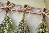 Various bright bouquet of dried flowers hanging on rope against wooden background, making dried flowers modern decoration for home interior closeup.
