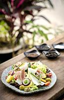 nicoise style healthy organic rustic salad with egg and ham outdoors.
