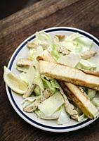 simple healthy orgaanic chicken caesar salad on wood table.