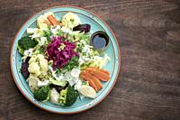 rustic cottage salad with healthy mixed steamed and fresh vegetables on colorful plate.