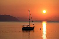 Beautiful sunrise in Aegean sea with boat and mountains, Turunc beach, Turkey.