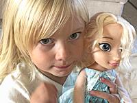 Four years old blond girl with her blond doll doll in Scania, Sweden, Scandinavia.