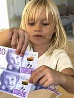 Blond girl, four years old, holding Swedish banknotes in Ystad, Scania, Sweden, Scandinavia.